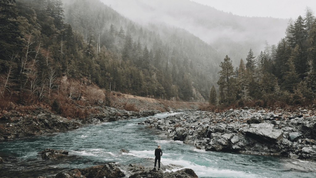 man standing in front of foggy river and mountains