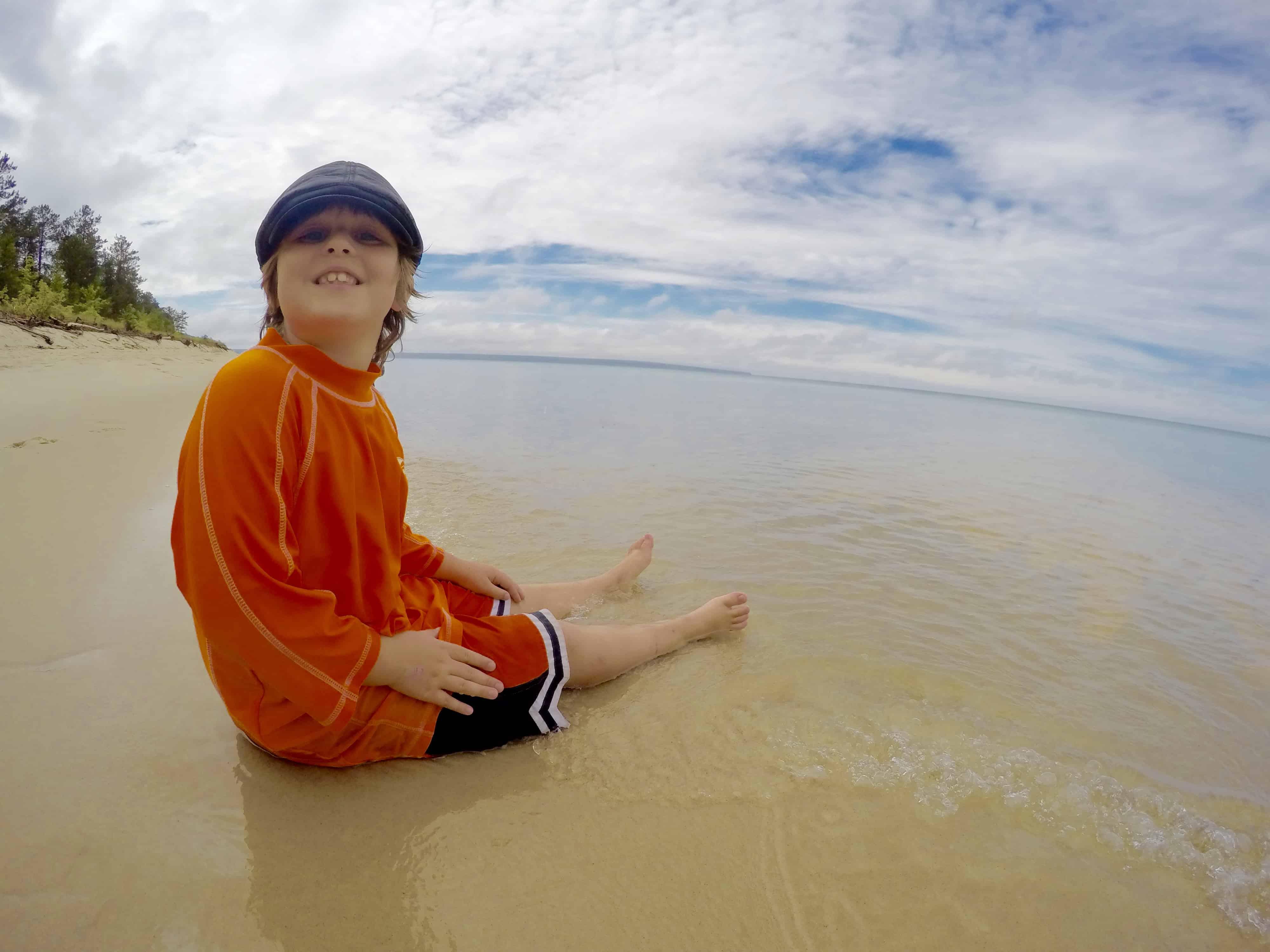 boy sitting on Miner's Beach in Michigan on Lake Superior