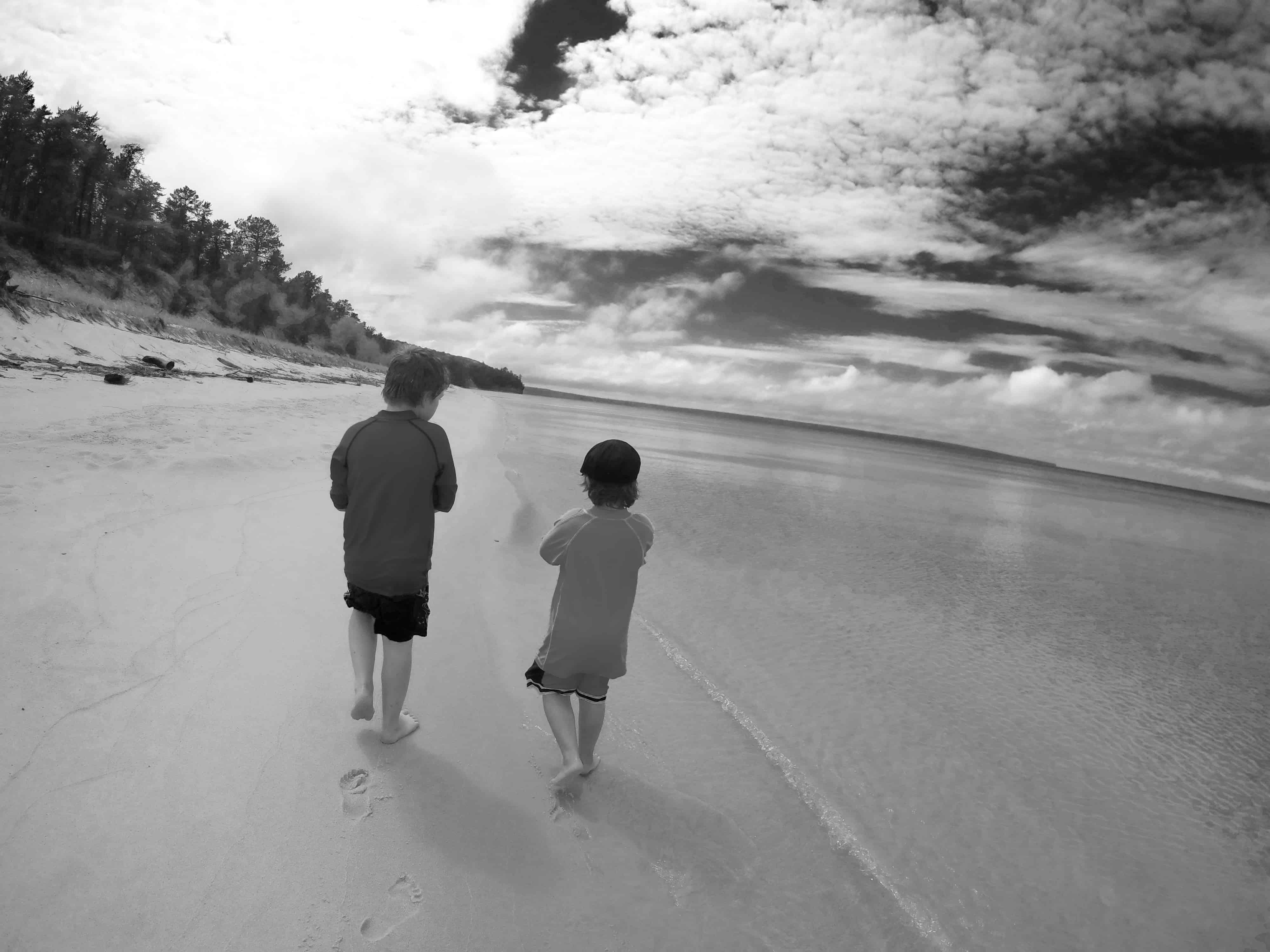 black and white photo of boys on Michigan beach