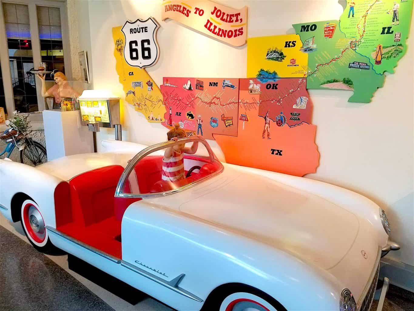 vintage white car next to Route 66 map in Joliet