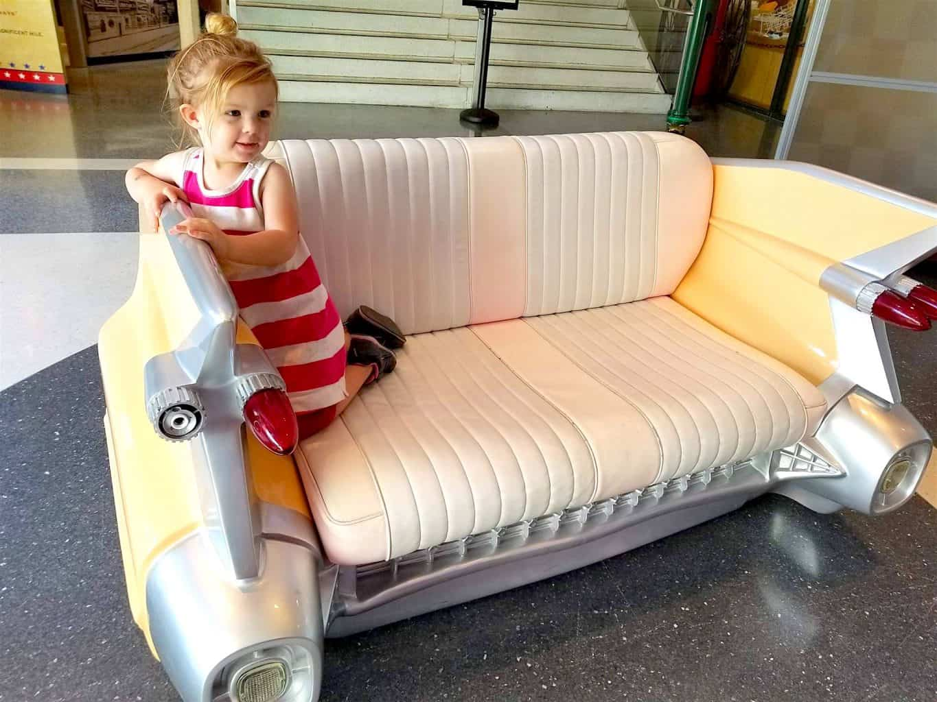 little girl on vintage car couch at a museum