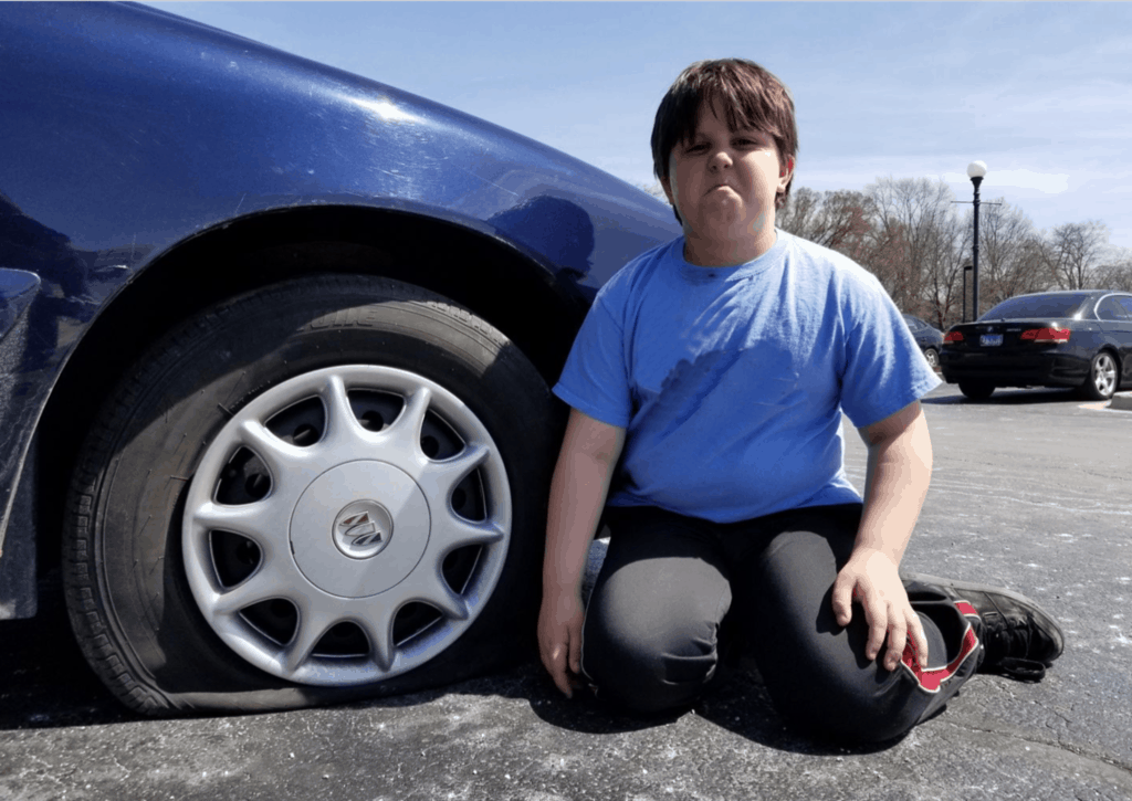 boy next to flat tire on car