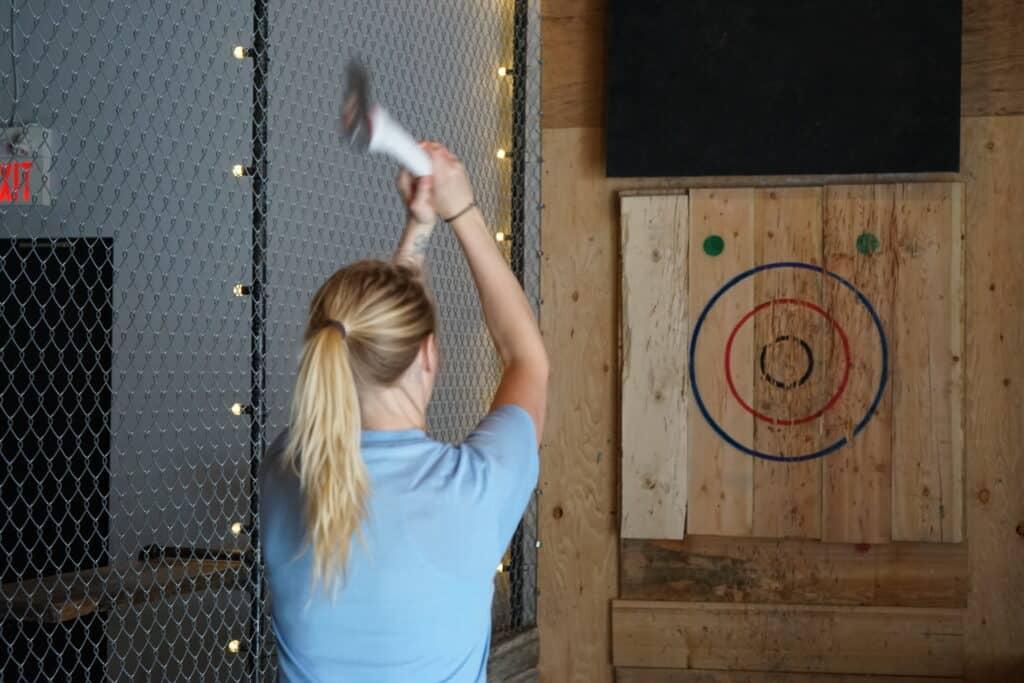 woman throwing axe at bullseye