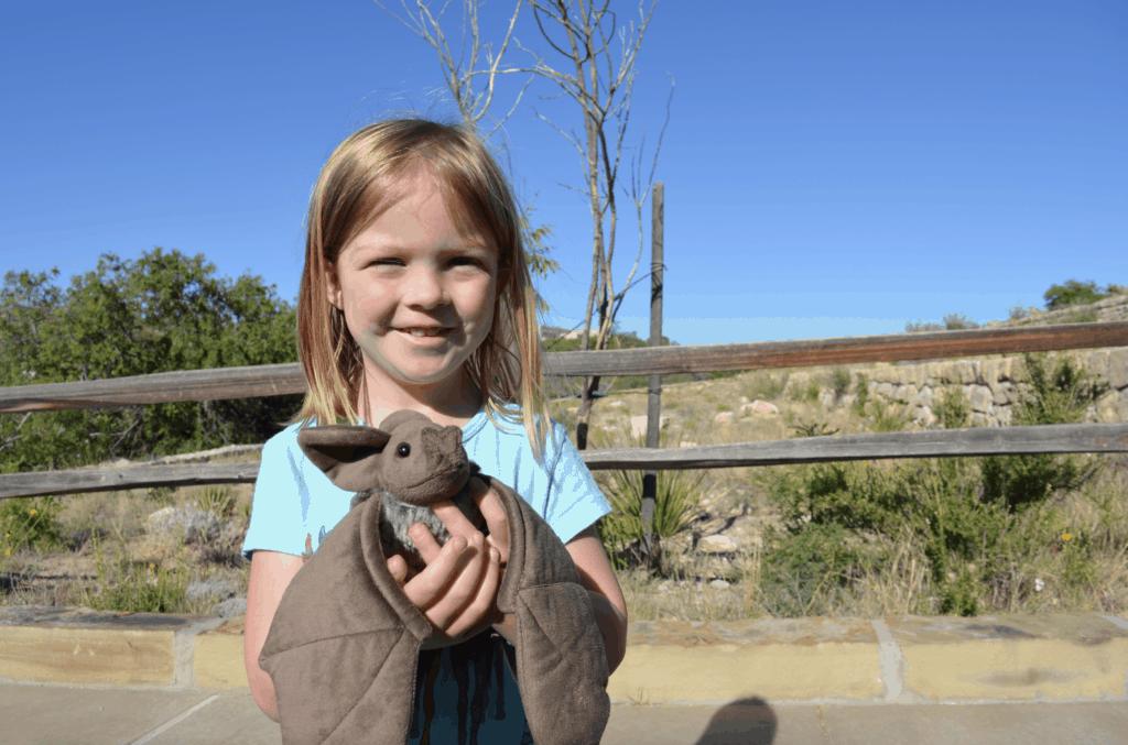 girl holding plush stuffed animal bat