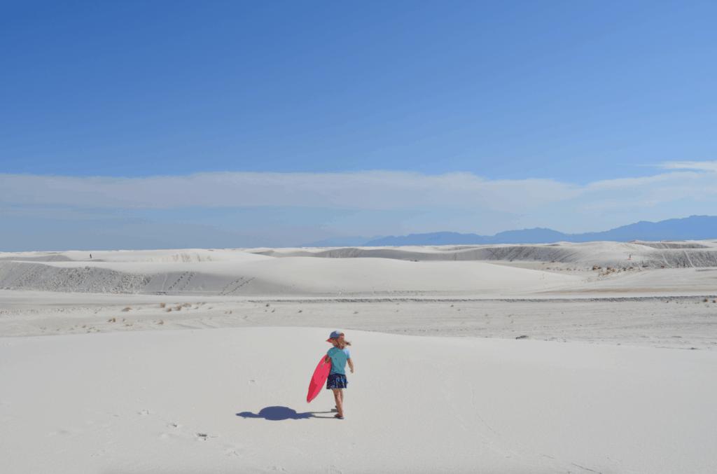 girl holding pink sled in white sand
