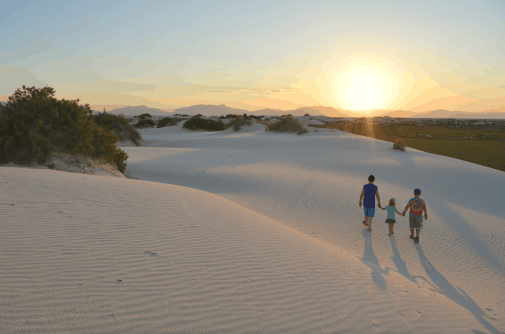 kids holding hand on white sand at sunset
