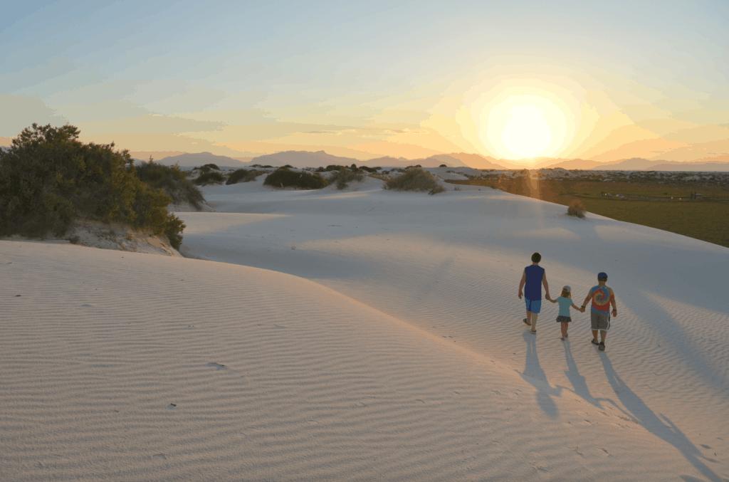 kids holding hand on white sand at sunset