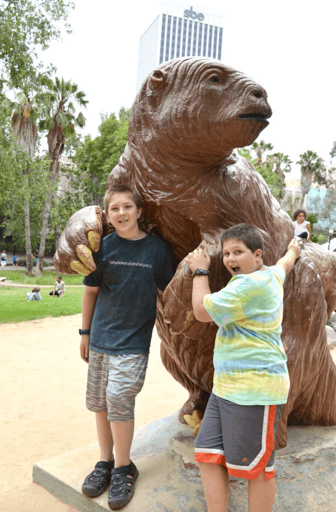 teen boys posing with large animal statue