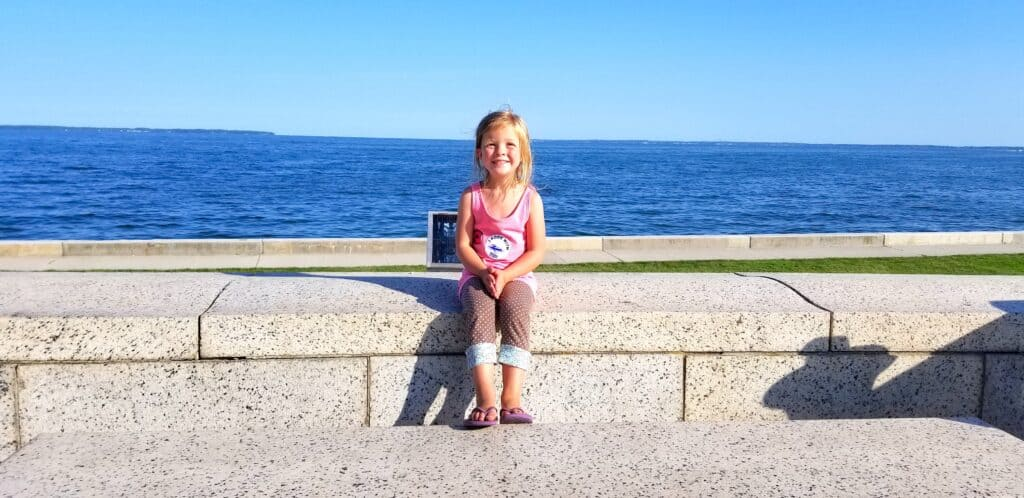 girl sitting on wall in front of Lake Erie