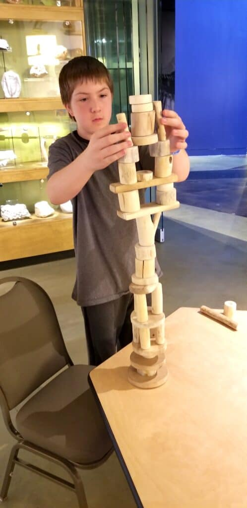 teen boy building wood tower