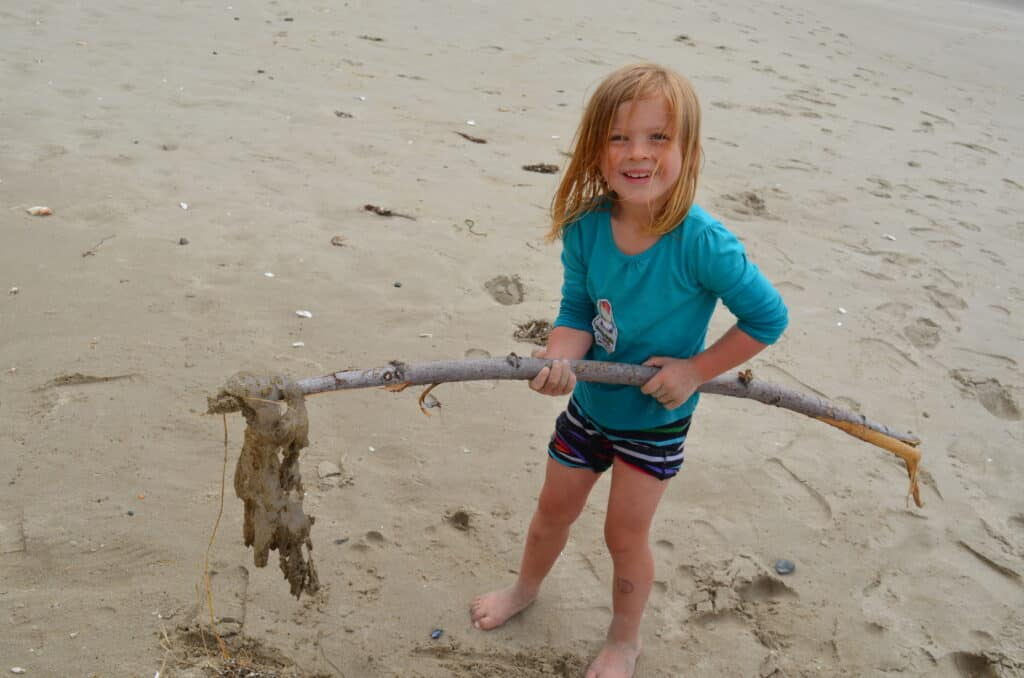 girl on beach holding jellyfish