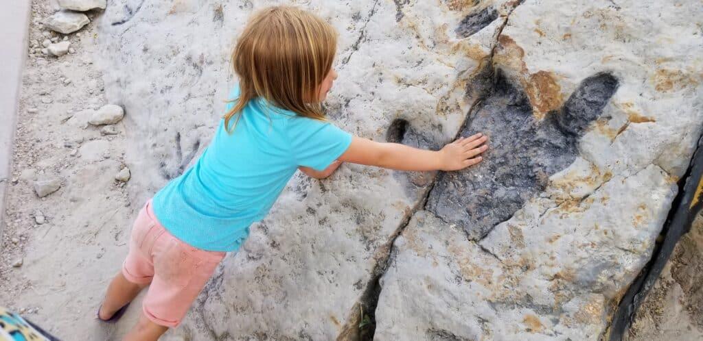 girl with hand on dinosaur footprint track
