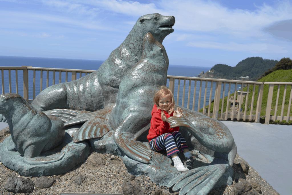 girl sitting on sea lion statue Oregon