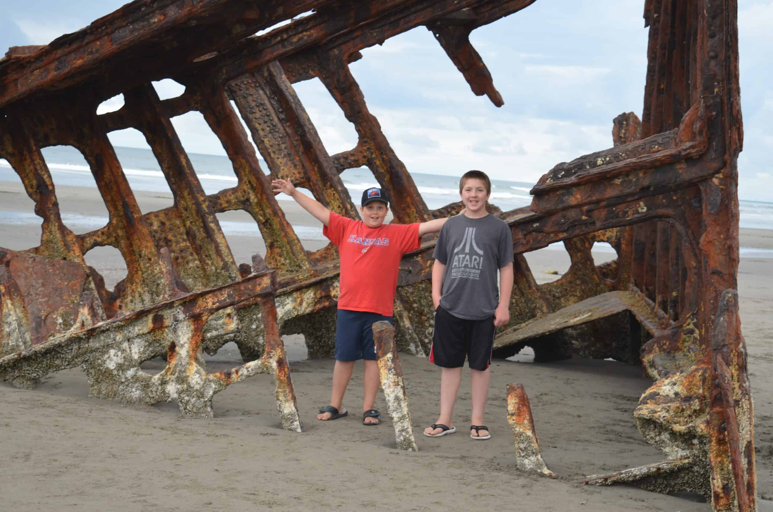 two boys standing in front of Peter Iredale Shipwreck