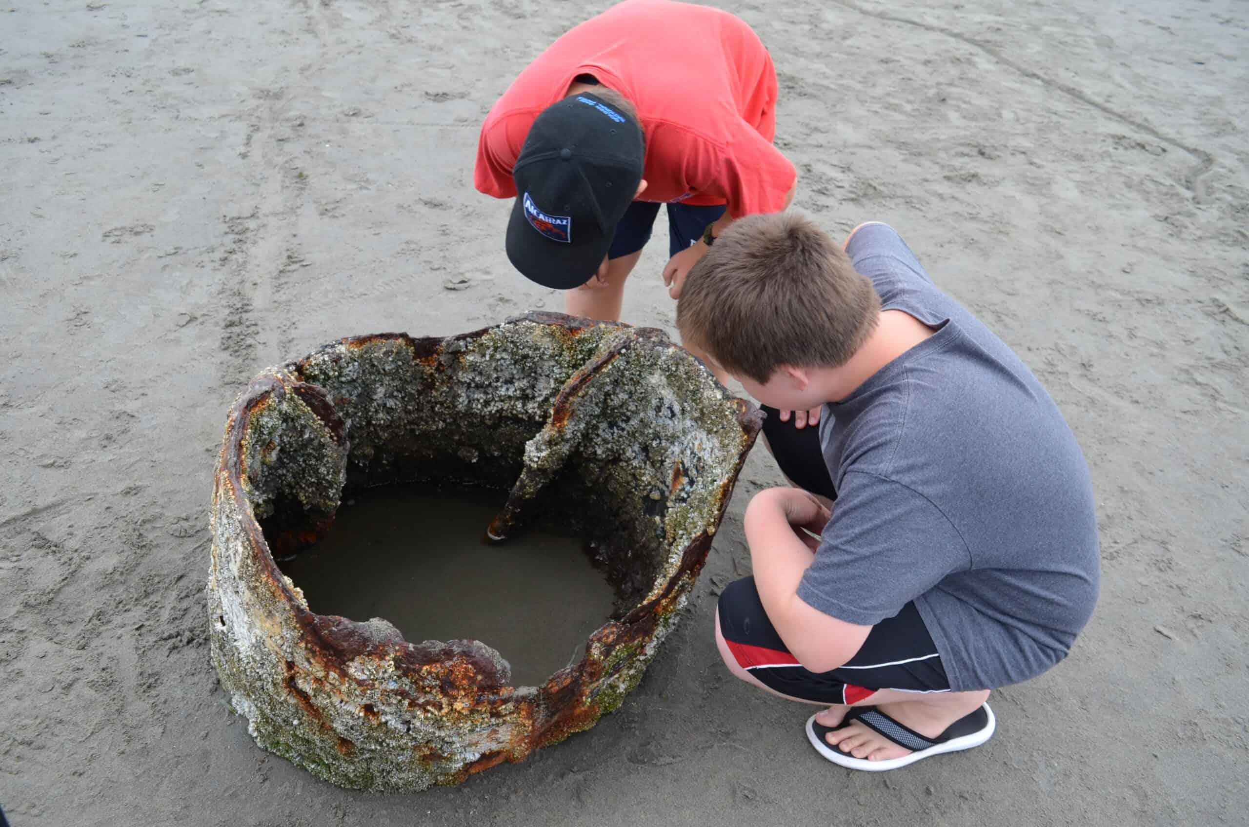 boys looking inside rusty shipwreck