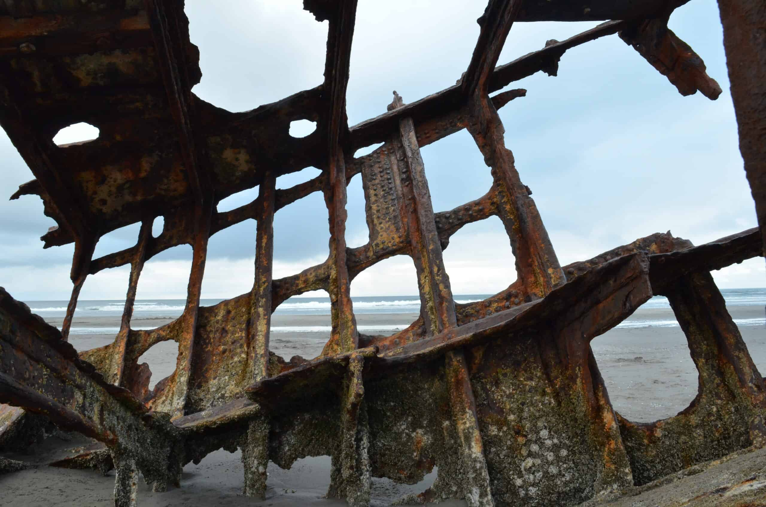 close up of rusty shipwreck remains on beach